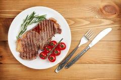 牛腰肉排用迷迭香和西红柿在板材 库存图片