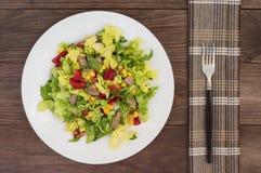 从牛舌肉、大白菜、胡椒、玉米、荷兰芹和蓬蒿的沙拉 木背景 顶视图 免版税库存照片