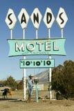牛仔倾斜反对在沙子汽车旅馆标志前面的岗位与$10的RV停车处,在路线54 & 380的交叉点在Carrizozo 免版税库存图片