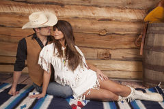 牛仔和印地安妇女坐前面准备亲吻 免版税库存图片