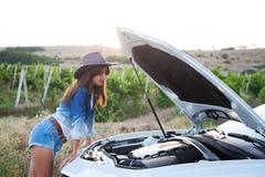 牛仔女孩看机动车 图库摄影