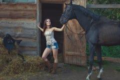 牛仔妇女拿着一匹马 库存照片