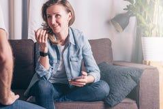 牛仔布夹克的年轻微笑的妇女坐长沙发在屋子里和谈话与坐在她前面的一个人 库存图片
