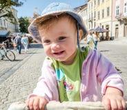 牛仔布帽子和夹克的笑那的一个愉快的矮小的女婴的画象表现出您的情感,走在市场Squar上 库存照片