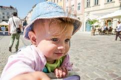 牛仔布帽子和夹克的笑那的一个愉快的矮小的女婴的画象表现出您的情感,走在市场Squar上 免版税库存图片