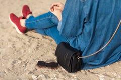 牛仔布成套装备时尚细节 后面有红色闪烁修指甲的看法时髦的妇女在拿着太阳镜和皮革的海军牛仔裤小 库存图片