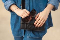 牛仔布成套装备时尚细节 有红色闪烁修指甲的时髦的妇女在拿着太阳镜和皮革小发怒人体的海军牛仔裤 免版税库存照片