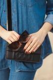 牛仔布成套装备时尚细节 有红色闪烁修指甲的时髦的妇女在拿着太阳镜和皮革小发怒人体的海军牛仔裤 免版税库存图片