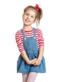 牛仔布礼服的可爱的矮小的白肤金发的女孩 免版税库存图片
