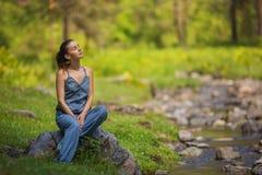牛仔布礼服的女孩坐石头在一条小河附近在森林里 免版税库存图片