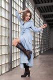 牛仔布礼服的快乐的与腿的女孩和起动提高了看d 免版税库存图片