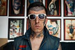 牛仔布背心和太阳镜的纹身花刺艺术家 库存图片