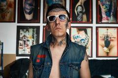 牛仔布背心的纹身花刺艺术家在演播室 库存照片