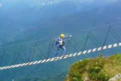 牛仔布衣服、盔甲和抢救绳索的一个年长人是索桥高在山 库存照片