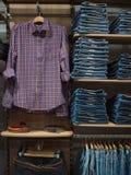 牛仔布衣物在商店 有整洁地安排的商店与casu 免版税库存照片