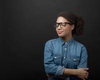 牛仔布衬衣佩带的玻璃的少妇 免版税图库摄影