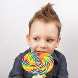 牛仔布衬衣的一个男孩吃棒棒糖的 库存图片