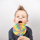 牛仔布衬衣的一个男孩吃棒棒糖的 库存照片