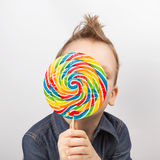 牛仔布衬衣的一个男孩吃棒棒糖的 免版税库存图片