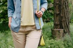 牛仔布衬衣的妇女和一件黄色T恤杉和裤子走在绿色公园的 免版税库存照片