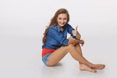 牛仔布青少年的女孩样式画象在给您拇指的地板上的 库存照片