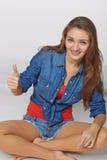 牛仔布青少年的女孩样式画象在给您拇指的地板上的 免版税库存照片