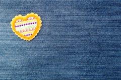 牛仔布-与被绣的心脏的背景 库存图片