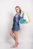 牛仔布总体的美丽的白肤金发的女孩和拿着多彩多姿的购物袋的一件紫色衬衣 愉快的女孩去购物 免版税库存照片