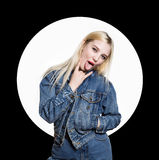 牛仔布jaket和牛仔裤的年轻白肤金发的妇女显示在两个手指之间的舌头在白色背景 猥亵生活方式 库存照片