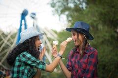 牛仔帽的两个美丽的女孩吃冰的 免版税库存图片