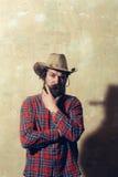 牛仔帽的有胡子的人和在墙壁上的黑阴影 免版税图库摄影