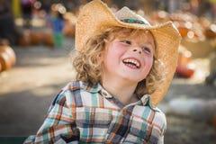牛仔帽的笑的男孩在南瓜补丁 库存图片