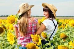 牛仔帽的美丽的女孩在向日葵领域 免版税库存照片