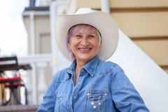 牛仔帽的年长妇女,看照相机和微笑 在露天 免版税库存图片