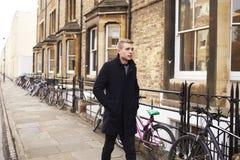牛津英国2016年10月26日:走沿住宅街道的年轻人在牛津 免版税库存图片