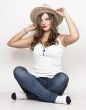 牛仔裤、白色T恤杉和牛仔帽的美丽的卷曲女孩 库存照片