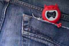 从牛仔裤口袋的红魔逃命 库存图片