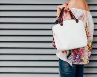 牛仔裤和一件时兴的色的女衬衫的一个女孩有摆在反对白色背景的一个时兴的白色提包的  免版税图库摄影