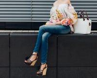 牛仔裤和一件时兴的色的女衬衫的一个长腿的女孩有一双时兴的白色提包和难以置信的鞋子的坐 库存照片