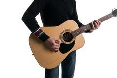 牛仔裤和一件黑毛线衣的,戏剧一个吉他弹奏者有一个滑子的一把声学吉他,在框架的中心,在一白色backgroun 免版税库存照片