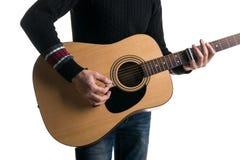 牛仔裤和一件黑毛线衣的,戏剧一个吉他弹奏者有一个滑子的一把声学吉他,在框架的中心,在一白色backgroun 库存照片