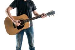 牛仔裤和一件黑T恤杉的,戏剧一个吉他弹奏者一把声学吉他,在框架的左边,在白色背景 horizont 免版税库存照片