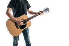 牛仔裤和一件黑T恤杉的,戏剧一个吉他弹奏者一把声学吉他,在框架的左边,在白色背景 horizont 库存照片
