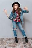 牛仔裤和夹克的迷茫的恼怒的年轻深色的夫人 免版税库存照片