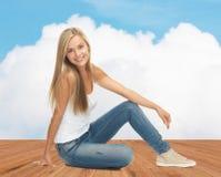 牛仔裤和白色无袖衫的愉快的少妇 库存照片