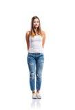 牛仔裤和白色汗衫的常设十几岁的女孩,被隔绝 免版税库存照片