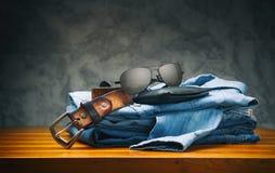 牛仔裤和衬衣有棕色传送带、钱包和太阳镜的在木桌上 免版税库存图片