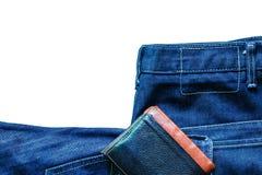 牛仔裤和钱包在白色背景 免版税图库摄影