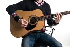 牛仔裤和黑色毛线衣的一个吉他弹奏者在框架的中心弹有滑子的一把声学吉他坐一把椅子在a的 库存图片