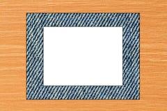 牛仔裤在胶合板和白色背景构筑 库存照片